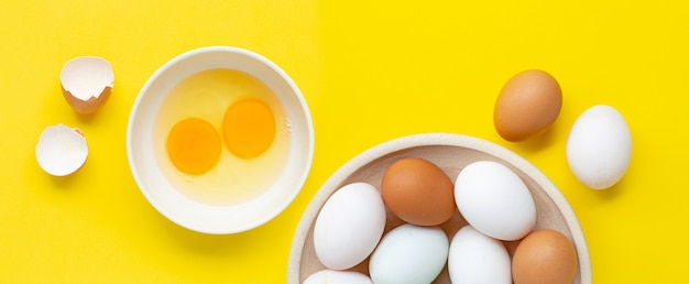 Fresh eggs on yellow background.