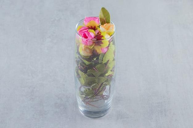 Fiori freschi ed eleganti in un bicchiere, sul tavolo bianco.