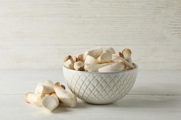 흰색 나무 배경, 텍스트를위한 공간에 그릇에 신선한 eringi 버섯