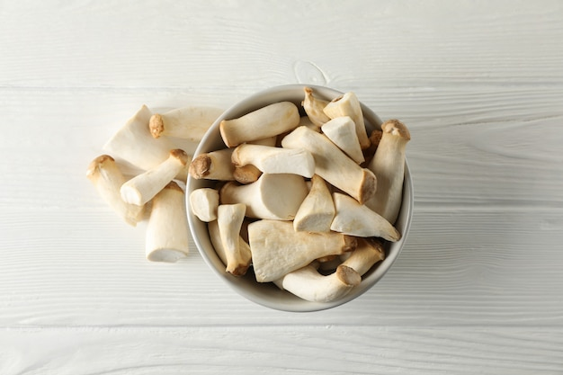 흰색 나무 배경, 평면도에 그릇에 신선한 eringi 버섯