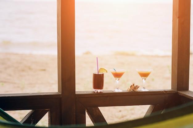 木製の端に新鮮なエキゾチックなカクテル。眼鏡の間に横たわるシェル。ストローとレモンのコーラ
