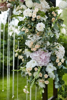 Fresh exotic flowers on the wooden wedding arch outdoors