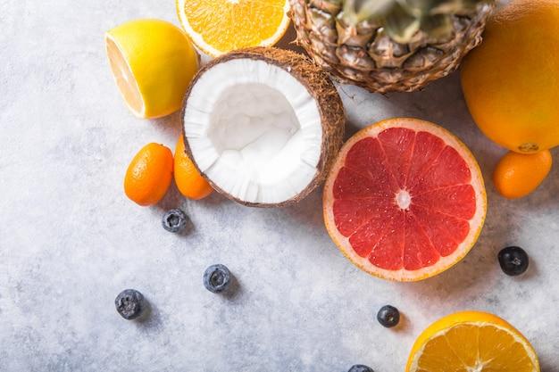 パステルグレーの背景-パイナップル、グレープフルーツ、ココナッツ、オレンジの新鮮なエキゾチックなフルーツ。モックアップ、フラットレイ、オーバーヘッド。上面図。