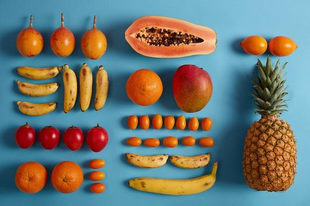 Свежие экзотические фрукты на синем фоне. ананас, папайя, бананы, кумкват, фортунелла, источник витаминов. летняя тропическая композиция. фрукты для приготовления сока или смузи. концепция питания. плоская планировка
