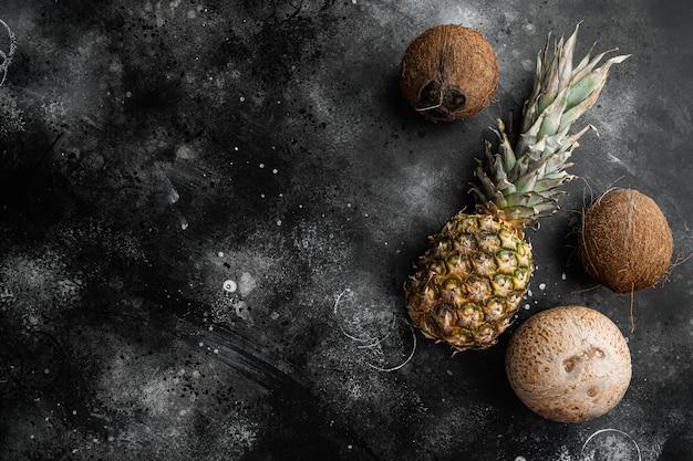 신선한 이국적인 과일, 파인애플과 코코넛 세트, 검은 색 어두운 돌 테이블 배경, 텍스트 복사 공간 평면도 평면 누워