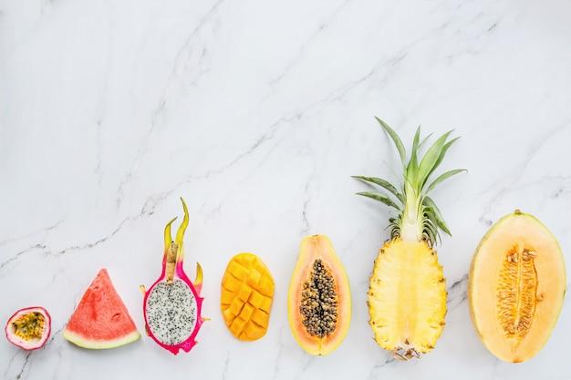 Fresh exotic fruits on white marble background