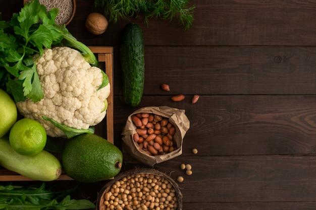Fresh farm vegetablescauliflower, greens, avocado, cucumber, cereals in a box on wood