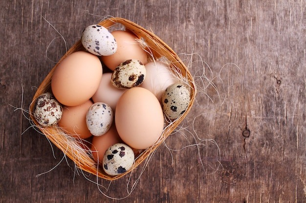 Fresh farmer eggs of chicken and quail in a basket on a dark background