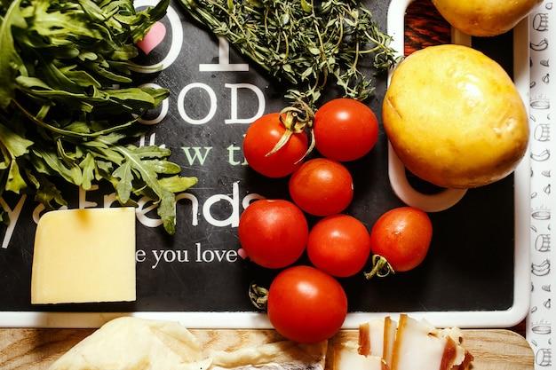 新鮮な農民は赤いテーブルの上にチーズと果物や野菜を販売しています
