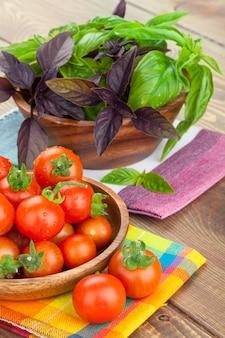 나무 테이블에 신선한 농부 토마토와 바질