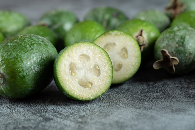 Fresh feijoa fruits on marble surface.