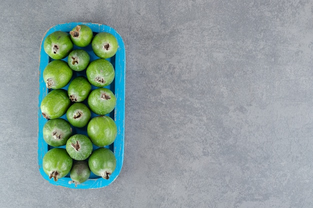 Свежие фрукты фейхоа на синей тарелке. фото высокого качества