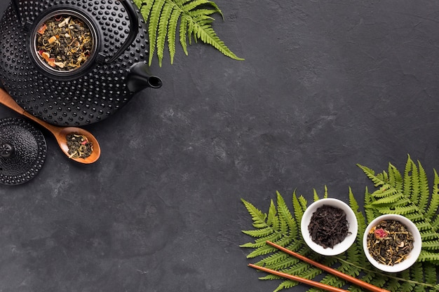 Fresh fern leaves and tea herb with black teapot on black slate background