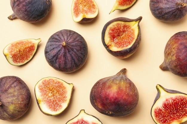 Свежие плоды инжира и ломтики на бежевом, вид сверху