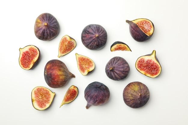 Свежие плоды инжира и ломтики на белом, вид сверху