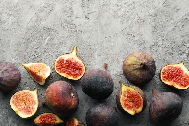 Fresh fig fruits and slices on gray, top view