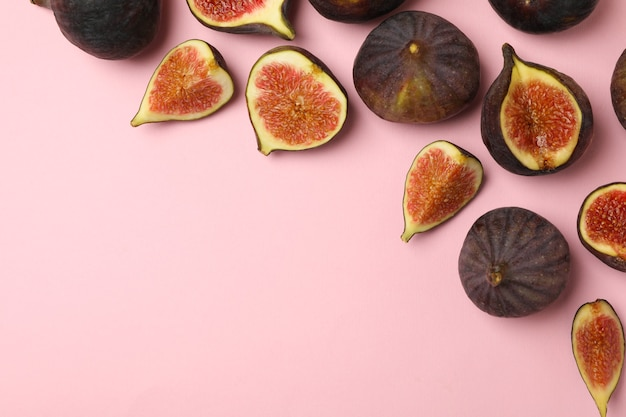 Fresh fig fruits and slices on pink, copy space