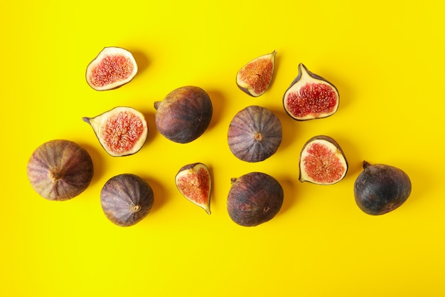 Fresh fig fruits and slices on yellow, top view
