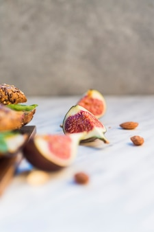 Fresh fig slices and almonds near hot dog on wooden board over white background