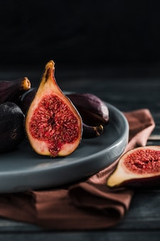 Fresh figs are whole and cut into slices on plate in a low key