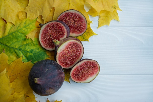 Fresh figs in the autumn leaves. autumn . . autumn . layout for seasonal offers and holiday cards, top view. space for text.