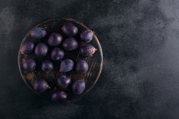 Fresh figs in a bowl on a dark wood, top view with copy space