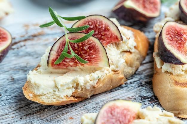 Свежий инжир, брускетта со сливочным сыром на деревянном столе, итальянское меню брускетты, рецепт, вид сверху