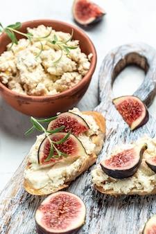 Fresh figs, cream cheese bruschetta on wooden table, italian bruschetta menu, recipe, top view