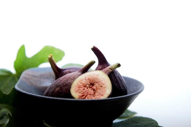 白いテーブルの上のイチジクの葉を持つボウルに新鮮なイチジク。健康的なスナックと食べ物。テキスト用の空スペース
