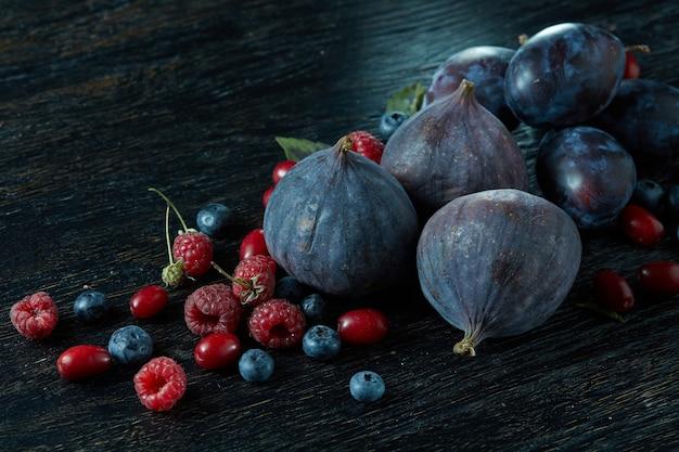 ダークウッドのテーブルにさまざまな品種の新鮮なイチジクの果実