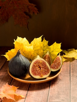 Fresh figs on a plate with yellow autumn leaves wooden rustic surface