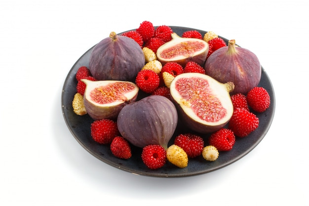 Fresh figs, strawberries and raspberries on blue ceramic plate isolated on white background