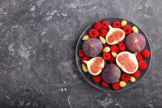 Fresh figs, strawberries and raspberries on blue plate on black concrete background
