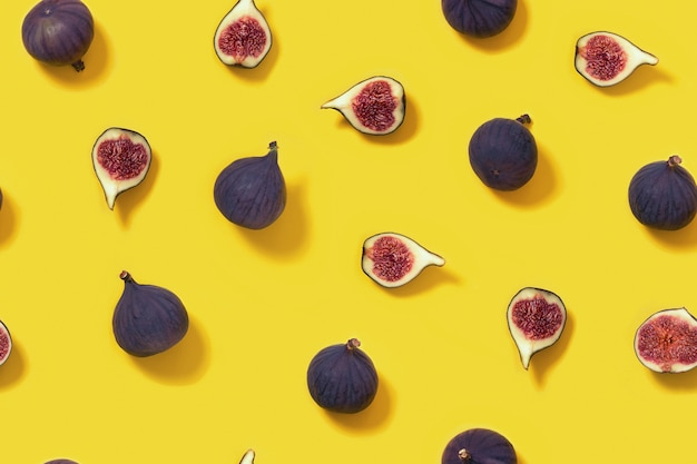 新鮮なイチジク全体と黄色の背景にスライスしたイチジク。食品のシームレスなパターン。