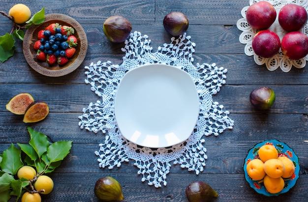 桃、アプリコット、ブルーベリー、イチゴ、木製の背景と新鮮なイチジク。
