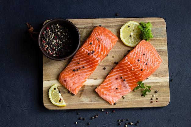 Свежее филе красной рыбы со специями и лимоном, на деревянной разделочной доске. серый фон. вид сверху.
