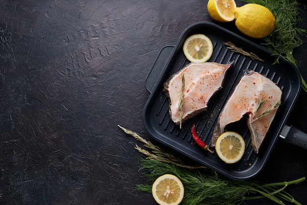 Fresh fillet of sea fish in a grill pan on dark background.