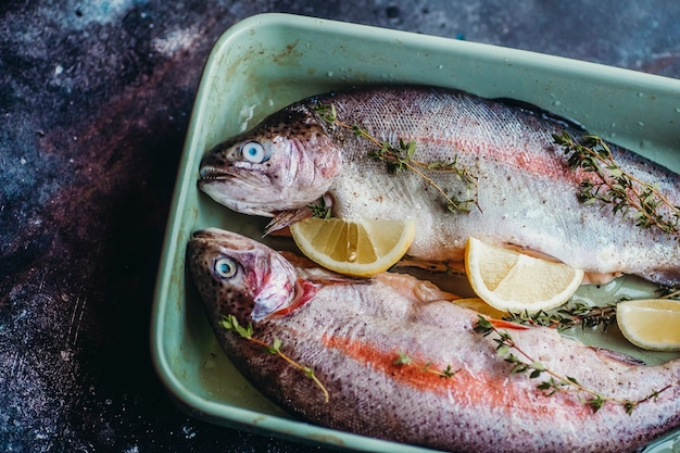 ハーブ、コショウ、タイム、レモンで味付けした、調理前の新鮮な魚。
