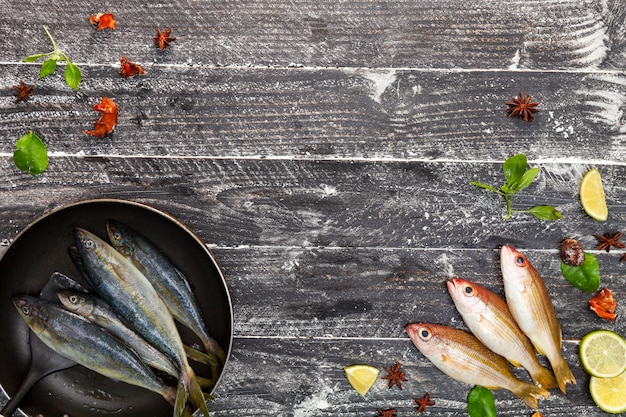 Fresh fish in black frying pan, fish with spices and vegetables, cooking background concept