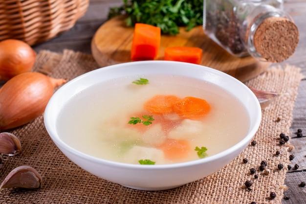 Бульон из свежей рыбы. рыбный суп с ингредиентами и специями для приготовления. деревянный фон