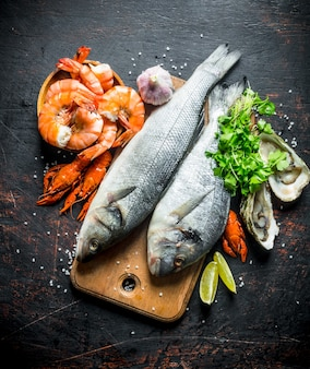 Fresh fish on cutting board with oysters, shrimp and crayfish on dark rustic table