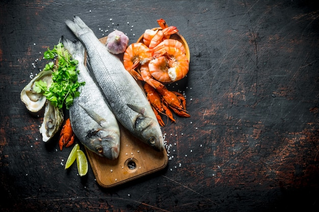 Fresh fish on a cutting board with oysters, shrimp and crayfish.