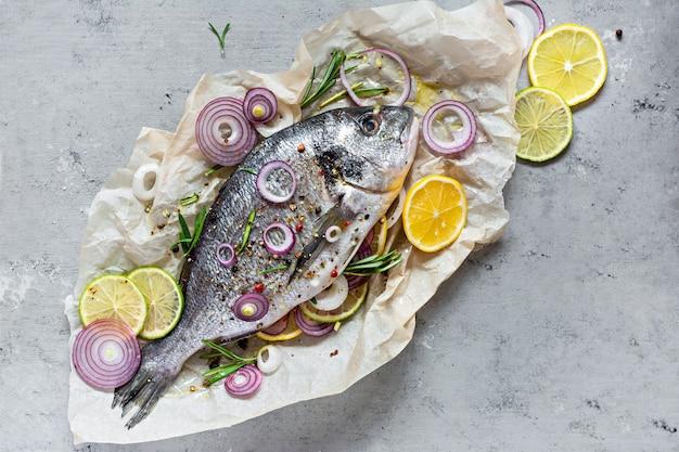 신선한 생선 황새. 허브, 향신료, 레몬과 라임 조각이 회색 배경에 요리 할 준비가 된 원시 황새.