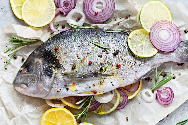 Fresh fish dorado. raw dorado with herbs, spices and lemon and lime slices ready to cook on a gray background.