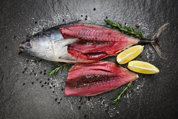 Fresh fish fillet sliced for steak or salad with herbs spices rosemary and lemon - raw fish seafood on black plate background , longtail tuna , eastern little tuna fillet ingredients for cooking food