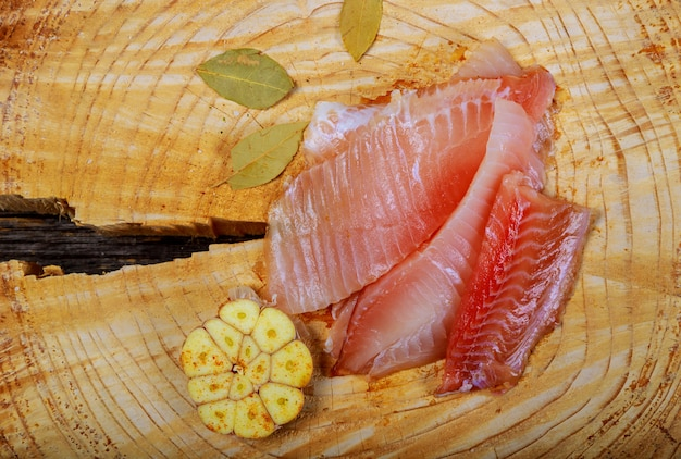 Fresh fish fillet tilapia with ingredients for cooking on wooden table