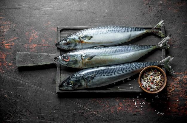新鮮な魚のサバとスパイス。暗い素朴なテーブルの上