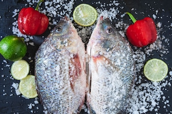 Fresh fish of tilapia with salt and seasoning for cooking.