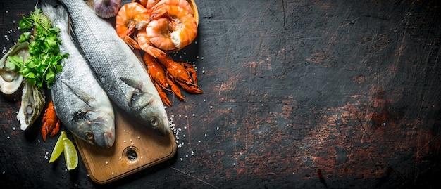 Свежая рыба на разделочной доске с устрицами, креветками и раками на черном деревенском столе