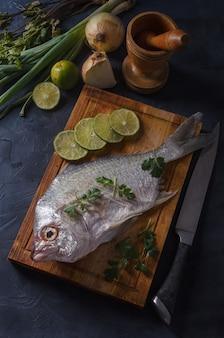 Свежая рыба на деревянной доске черного цвета с луком и лимоном